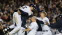 Jeter is mobbed by his teammates after winning the game with his second hit and third RBI of the night.